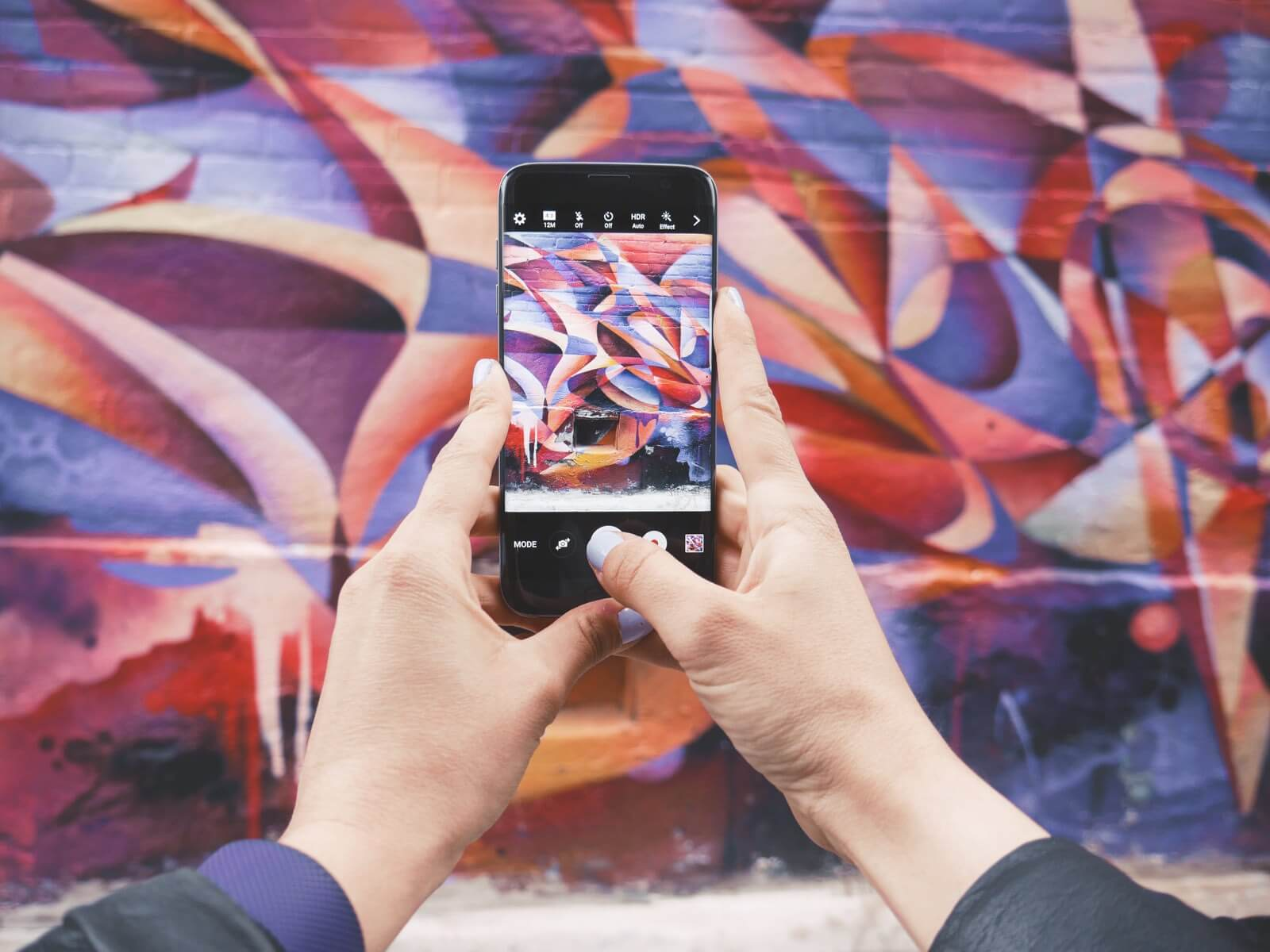 Hands holding a phone taking a picture of graffiti art